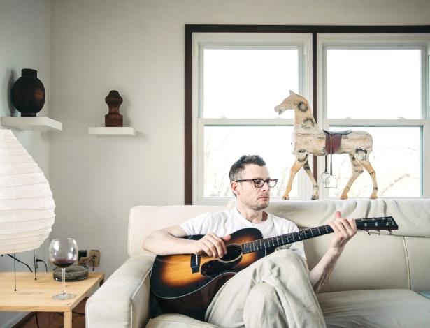 Erik Hagerman toca guitarra em sua casa, em Glouster, Ohio