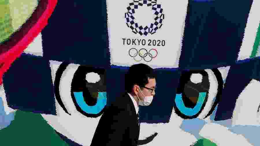 Pedestre caminha em frente a pôster da Olimpíada de Tóquio - Kim Kyung Hoon