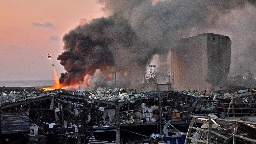 Helicóptero apaga o incêndio no local de uma explosão no porto da capital libanesa, Beirute - 4 de agosto de 2020 - STR / AFP