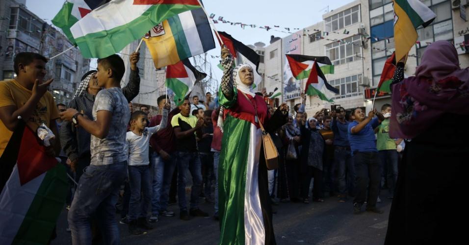 1º.out.2015 - Grupo dança na cidade de Ramallah, na Palestina, enquanto assiste ao pronunciamento do presidente Mahmud Abbas durante o hasteamento da bandeira palestina na sede das Nações Unidas, em Nova York, na quarta-feira (30). A ONU aprovou recentemente uma resolução que permite que as bandeiras da Palestina e da Santa Sé sejam hasteadas juntas com a dos Estados membros da organização