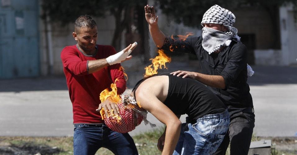 13.out.2015 - Jovens tentam apagar fogo no corpo de palestino que foi queimado ao tentar jogar uma bomba de coquetel molotov em soldados israelenses na cidade de Hebron, na Cisjordânia. O aumento da escalada da violência entre palestinos e israelenses na região abre precedentes para uma terceira Intifada, o levante mais radical dos palestinos