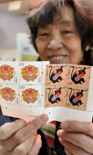 5.jan.2016 - Chinesa mostra série especial de selos lançados pela agência postal do país em homenagem ao ano do macaco, animal que rege 2016, segundo o horóscopo chinês