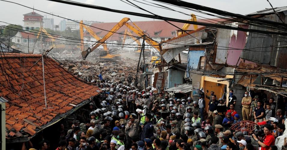 11.abr.2016 - Policiais fazem cordão de isolamento durante operação de demolição de construções irregulares em vila pesqueira de Jacarta, na Indonésia