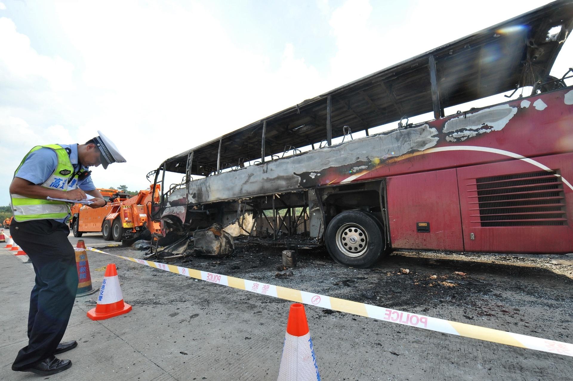 26.jun.2016 - Policial examina acidente em Yizhang, na província chinesa de Hunan. Um incêndio destruiu um ônibus de turismo, matando pelo menos 35 pessoas, incluindo duas crianças. O acidente aconteceu quando o ônibus colidiu com o corrimão do acostamento da estrada