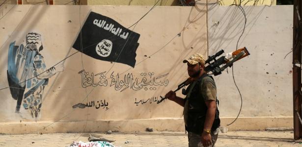 Integrante das forças de segurança do Iraque passa diante de muro pintado com a bandeira usada por militantes do Estado Islâmico, em Shirqat