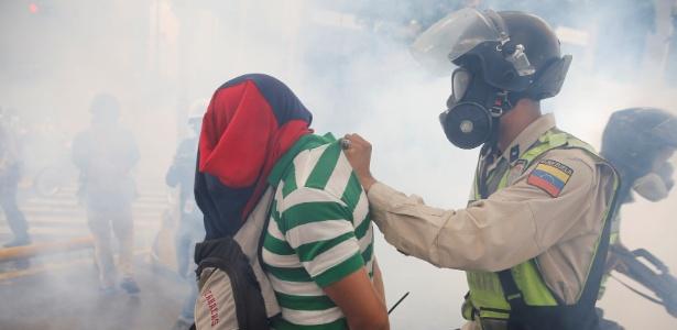 Policial detém manifestante durante ato contra o governo de Nicolás Maduro, em Caracas