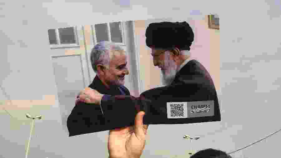 Manifestante segura foto do general Soleimani com o aiatolá do Irã, Ali Khamenai - ATTA KENARE / AFP
