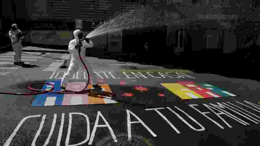 """Profissionais de saúde pública usam desinfetante para limpar uma rua, enquanto um grafite no chão diz """"Fique em casa, cuide da sua família"""", em La Paz, Bolívia - MANUEL CLAURE/REUTERS"""