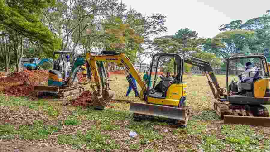 Novas covas são abertas por máquinas no cemitério da Vila Formosa na Zona Leste de São Paulo, neste sábado (18), para receber os sepultamentos decorrentes da pandemia de covid-19 no estado - Antonio Molina/Fotoarena/Estadão Conteúdo