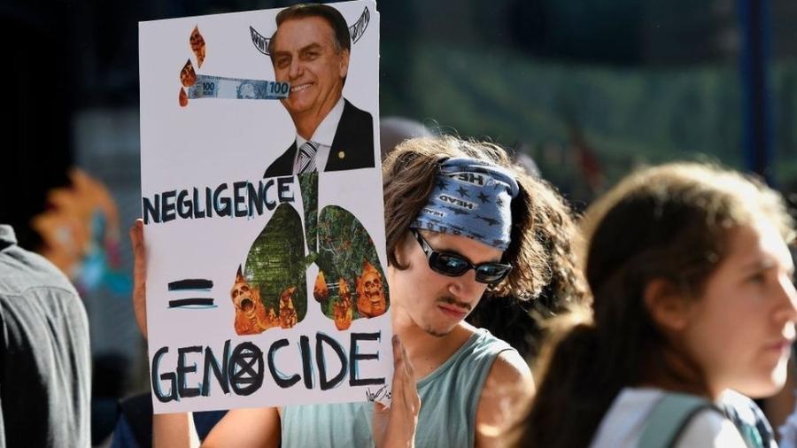 """Em Londres, ativista segura cartaz com foto de Bolsonaro e de florestas em chamas, com as palavras """"negligência"""" e """"genocídio"""" em inglês - Getty Images"""