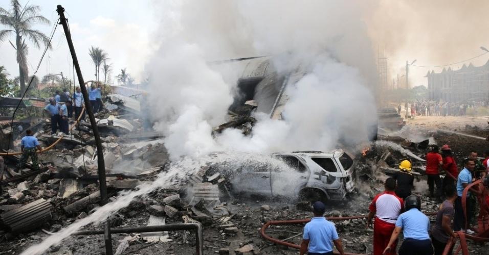 30.jun.2015 - Equipes de resgate tentam pagar incêndio causado pela queda do avião de transporte militar indonésio C-130 Hercules, em área residencial da cidade de Medan, na ilha de Sumatra, Indonésia. O acidente incendiou casas e veículos e matou mais de cem pessoas