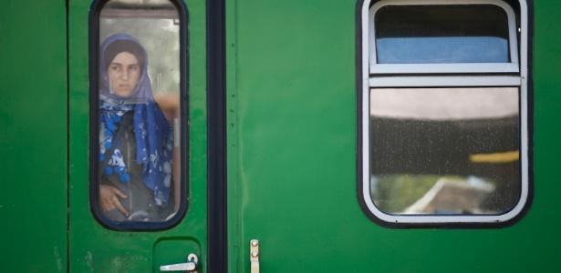 4.set.2015 - Uma imigrante observa a paisagem através da janela de um trem, na estação ferroviária Bicske, na Hungria - Leonhard Foeger/Reuters
