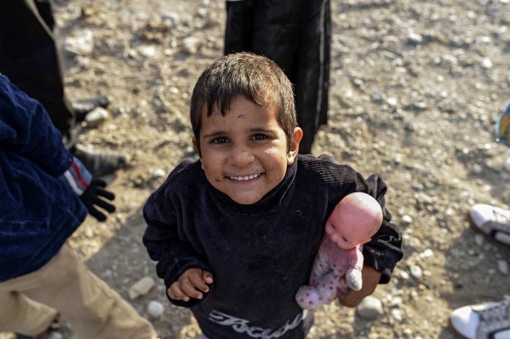 28.set.2015 - Menino refugiado brinca com boneca após atravessar a fronteira entre a Grécia e a Macedônia e se alojar em um campo de registro para imigrantes na cidade de Gevgelija