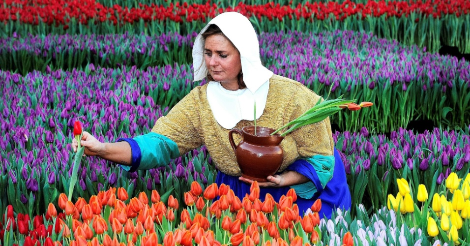 16.jan.2016 - Uma mulher vestida como uma camponesa retira camponesas que foram expostas em frente ao Palácio Real, em Amsterdã, na Holanda. O evento marca o início oficial, na região, da época da flor, que deve acabar no fim de abril
