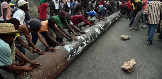Manifestantes usam poste para bloquear rua em Porto Príncipe, no Haiti