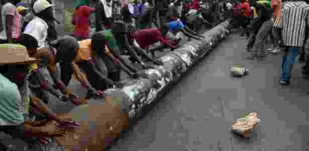 Manifestantes usam poste para bloquear rua em Porto Príncipe, no Haiti - HECTOR RETAMAL/AFP