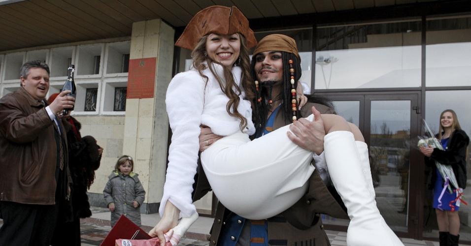 5.fev.2016 - 5.fev.2016 - German Yesakov, 25, ergue a mulher Anastasiya, 18, em seus braços do lado de fora do cartório na cidade russa de Stavropol. Yesakov escolheu esse traje para se casar com a amada e nem foi por causa do Carnaval