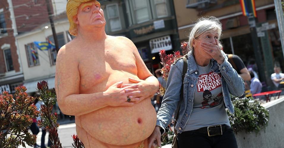 18.ago.2016 - Mulher posa para foto apontando o dedo para o órgão genital da estátua de Donald Trump, em San Francisco