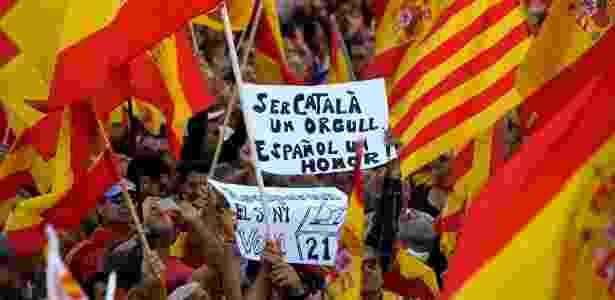 """29.out.2017 - Manifestante segura cartaz que diz """"Ser catalão é um orgulho, ser espanhol é uma honra"""" - Luis Gene/AFP"""