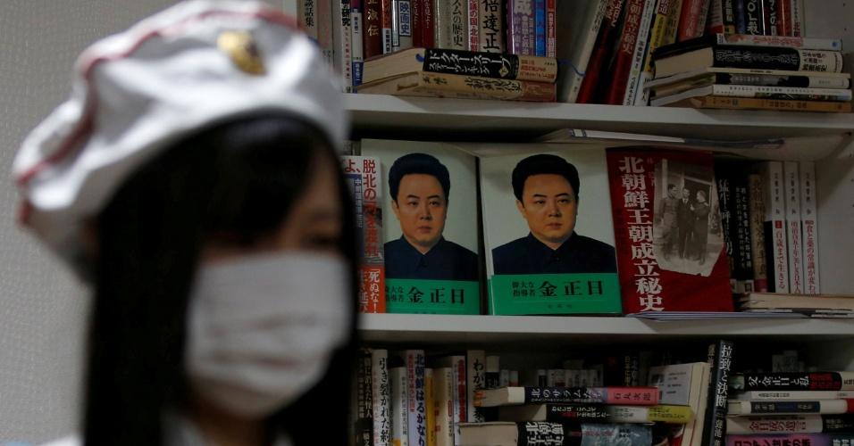 22.out.2017 - Jovem do fã clube da Coreia do Norte no Japão diante de estante com livros da Coreia do Norte, em Tóquio, no Japão