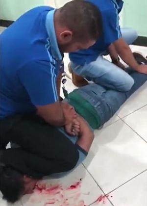Em um dos vídeos que circulam nas redes sociais, é possível ver dois seguranças em cima de Edicácio, que está deitado no chão com a boca sangrando e gemendo - Reprodução