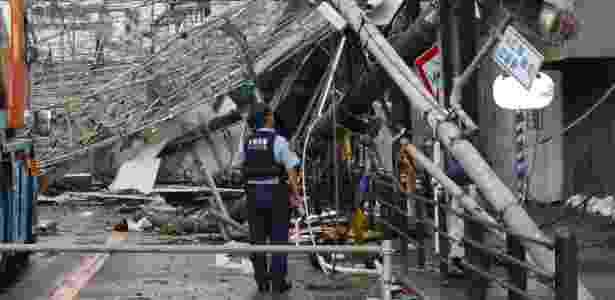 Policial observa os estragos feitos pelo tufão em Osaka, no Japão, na terça-feira (4), antes do terremoto - JIJI PRESS / AFP