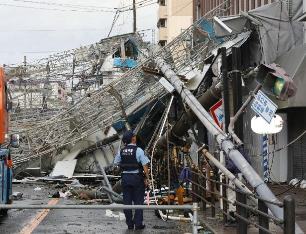 Policial observa os estragos feitos pelo tufão em Osaka, no Japão, na terça-feira (4), antes do terremoto