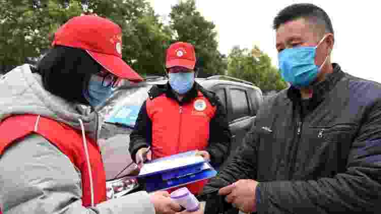 13.mar.2020 - Funcionária checa temperatura corporal de homem antes dele começar a trabalhar em Hefei, na China; número de casos de coronavírus no país passou para oito nas últimas 24 horas - Liu Junxi/Xinhua  - Liu Junxi/Xinhua