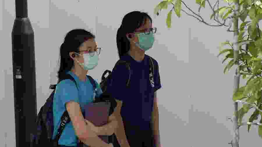 Estudantes que usam máscaras, como medida preventiva contra o novo coronavírus covid-19, voltam para casa da escola em Singapura em 25 de março de 2020 - ROSLAN RAHMAN/AFP