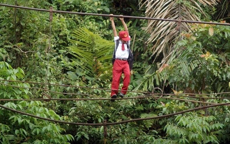 Indonésia - Estudantes de uma vila da ilha de Sumatra, Indonésia, precisam atravessar uma ponte de cordas, suspensa a uma altura de cerca de dez metros, para chegar à escola. A ponte fixa havia sido destruída e não foi reconstruída