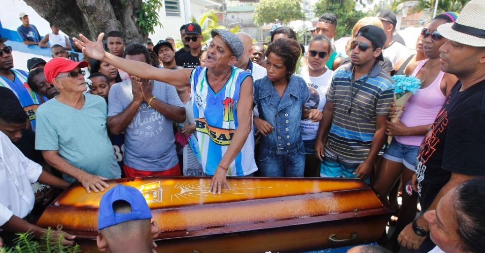 25.dez.2015 - O feirante Marcos dos Santos (de boina) se emociona durante o enterro do filho, Marcos Vinicius dos Santos, morto aos 11 anos em tiroteio na Cidade de Deus, no Rio de Janeiro.