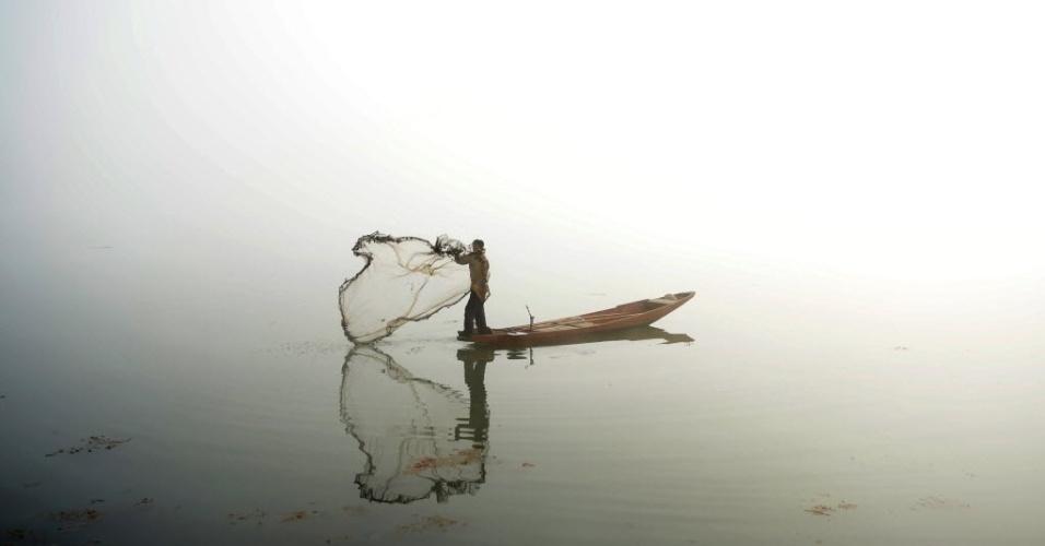 13.jan.2016 - Pescador lança redes em meio a densa neblina em um lago Srinagar, Índia