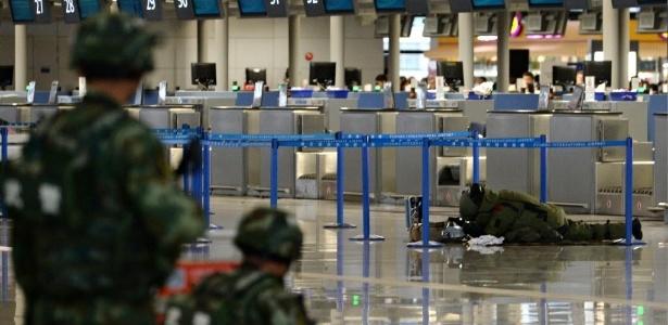 Especialista em desarmamento de bombas inspeciona uma bagagem deixada perto do balcão de check-in, após uma explosão no aeroporto de Pudong, em Xangai