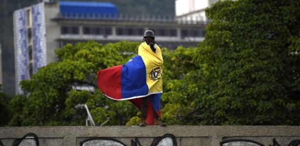 Manifestante se envolve na bandeira da Venezuela durante protesto contra o presidente Nicolás Maduro, em Caracas