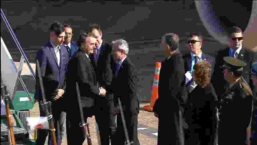 O presidente Jair Bolsonaro é acompanhado de seu filho mais novo, Jair Renan, na chegada à cúpula do Mercosul, em Santa Fé, na Argentina - Reprodução