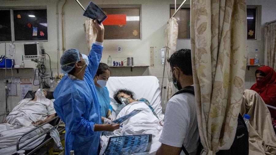 Médico olha o raio-X de um paciente durante turno de 27 horas no Holy Family Hospital em Nova Déli, Índia - Danish Siddiqui/Reuters