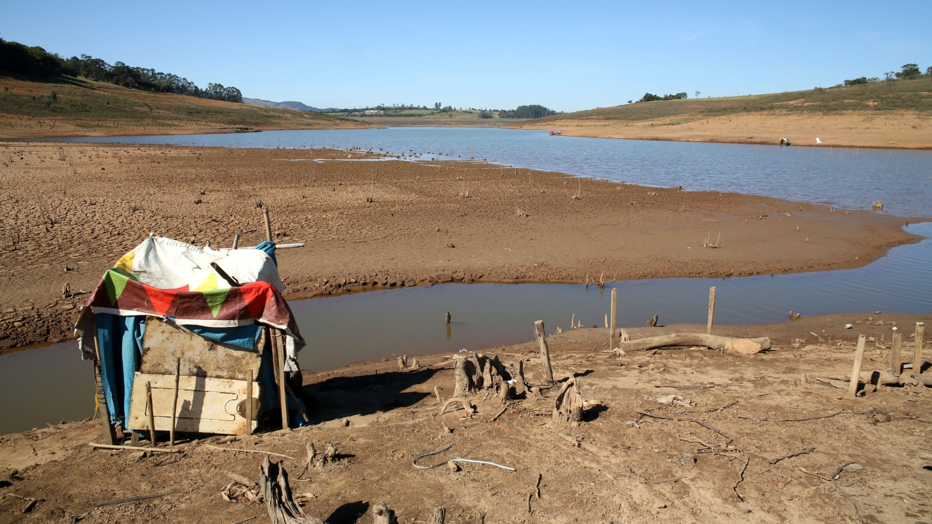 29.jul.2015 - O nível baixo da represa Jaguari-Jacareí, em Joanópolis (SP), permitiu a construção de um barraco em sua margem. A represa compõe o sistema Cantareira, que manteve o nível em 18,8% da água armazenada, segundo o índice tradicionalmente divulgado pela Sabesp. Esse número considera duas cotas do volume morto (de 182,5 bilhões de litros de água e de 105 bilhões), adicionadas no ano passado