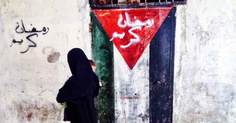 Com o filho no colo, mulher muçulmana cruza viela de Chatila, no Líbano, marcada por pintura da bandeira palestina