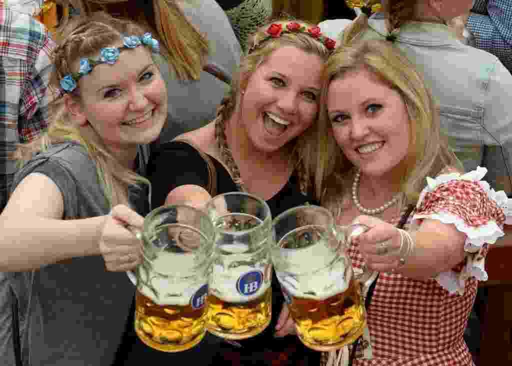 19.set.2015 - Participantes da Oktoberfest posam para foto com canecas de cerveja, em Munique, na Alemanha. O maior festival de cerveja do mundo começou neste sábado e vai até o dia 4 de outubro - Christof Stache/AFP Photo