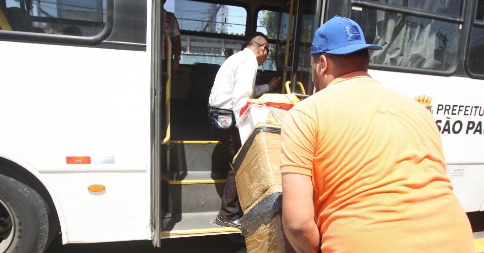15.out.2015 - Homem ajuda o vendedor a subir no ônibus com as caixas cheias de garrafas de água