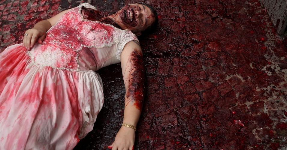 """2.nov.2015 - """"Noiva cadáver"""" deitada em calçadão da região central de São Paulo. A oitava edição da Zombie Walk acontece nesta segunda-feira (2) na capital paulista e no Rio de Janeiro"""