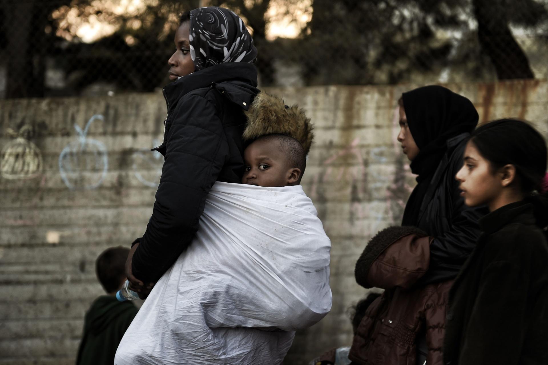 12.nov.2015 - Mulher carrega uma criança nas costas próximo a um centro de registro de imigrantes na ilha grega de Lesbos. A região se tornou porta de entrada de refugiados para a Europa