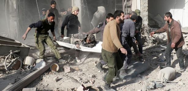 Sírios retiram homem ferido em maca após bombardeiro em bairro rebelde de Damasco, na Síria