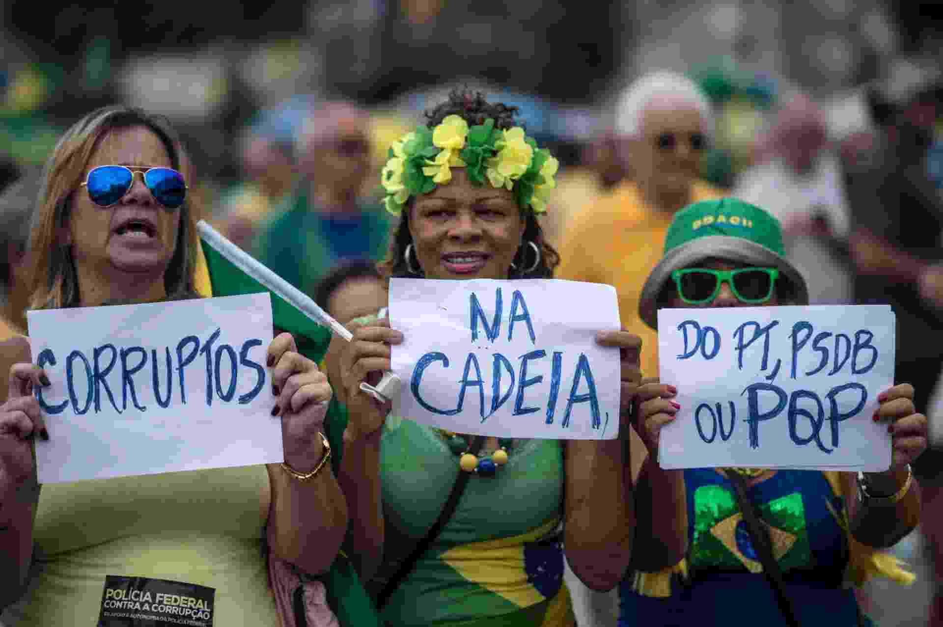 Essas mulheres foram à praia de Copacabana, na zona sul do Rio de Janeiro. Nos cartazes, elas pedem a prisão de todos os políticos envolvidos em corrupção, citando o PT e o principal partido da oposição, o PSDB - Christophe Simon/AFP