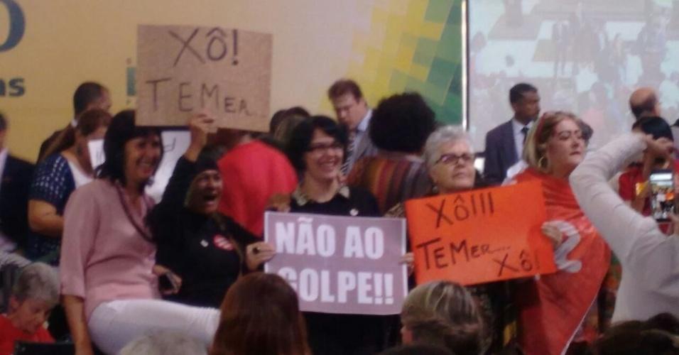 9.mai.2016 - Professores e técnicos de universidades federais levantam cartazes em protesto contra o impeachment da presidente Dilma Rousseff (PT) durante evento realizado no Palácio do Planalto, em Brasília (DF). Entre os alvos preferidos dos cartazes está o vice-presidente Michel Temer (PMDB)
