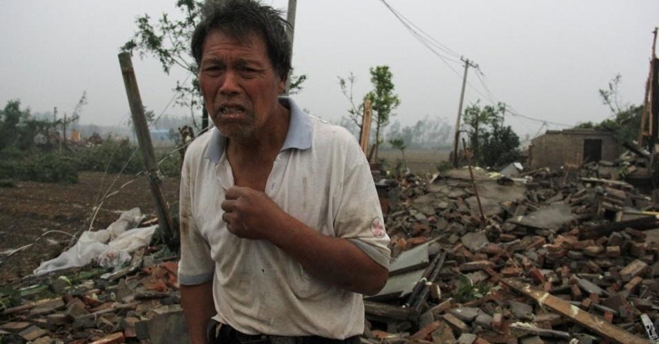 23.jun.2016 - Homem procura pertences em escombros de casa em Jiangsu, na China.  Pelo menos 51 pessoas morreram e dezenas ficaram feridas por causa de uma série de tempestades que afetaram o local