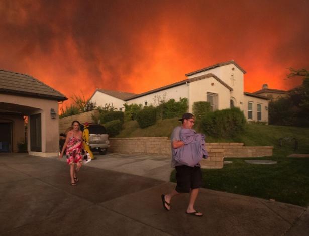 Residentes saem de casa enquanto chamas se aproximam de sua casa em Santa Clarita, na Califórnia