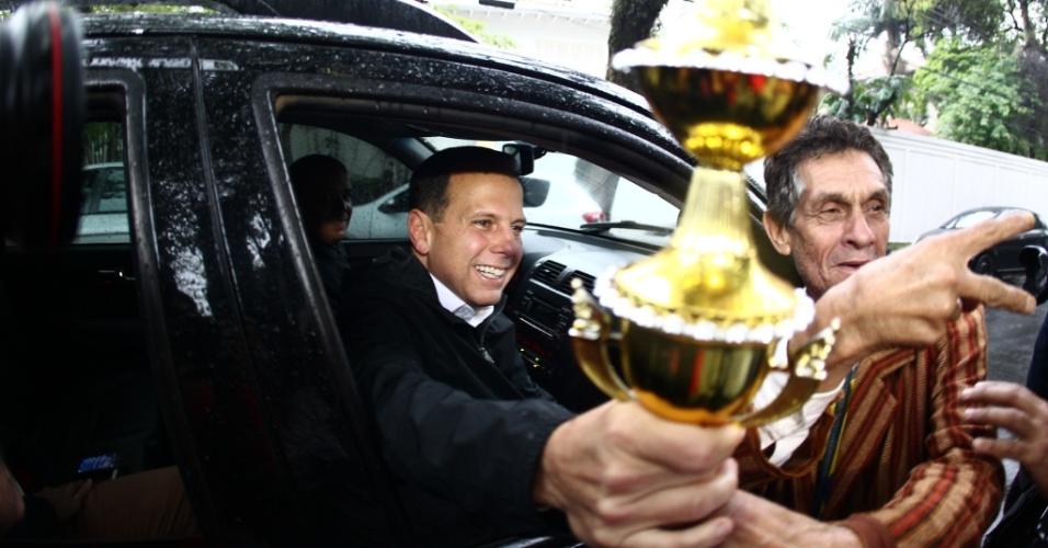 3.out.2016 - Após entrevista coletiva, o prefeito eleito de São Paulo, João Doria (PSDB), recebeu um troféu de um eleitor na rua. O tucano venceu a eleição municipal com 53,29% dos votos válidos