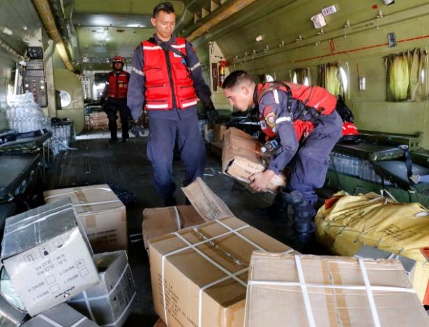 Funcionários carregam avião com donativos para o Haiti no aeroporto de Maiquetia, na Venezuela