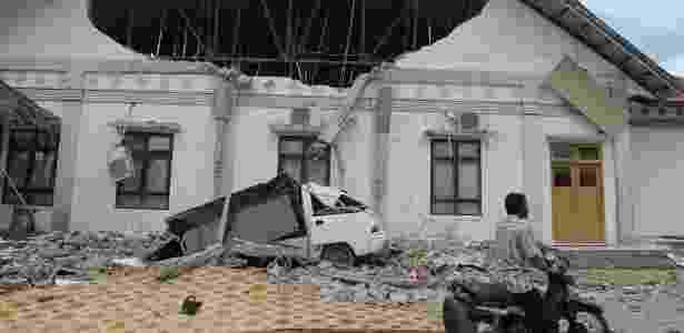 Homem passa diante de prédio destruído pelo terremoto em Pidie Jaya, na província de Aceh, Indonésia - Chaideer Mahyuddin/ AFP